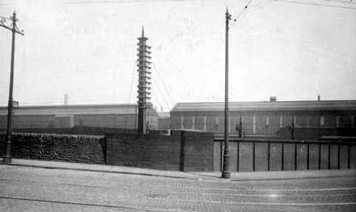 A view of Leeds Forge from Armley Road, showing long, low buildings behind a brick wall.