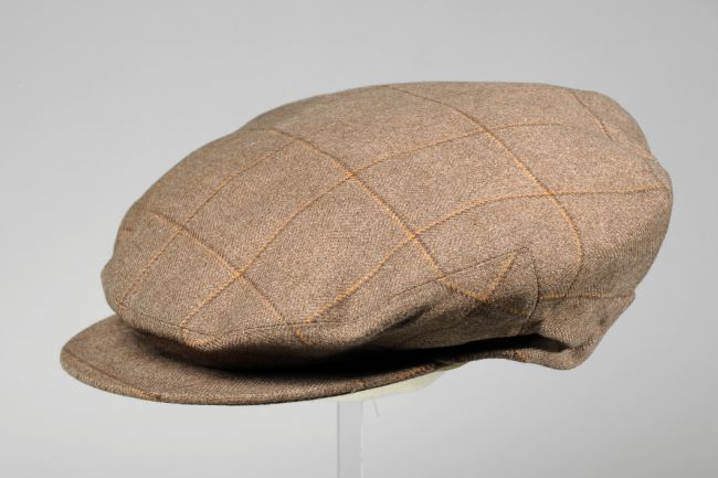 Flat cap in a light brown material, with thin dark brown and orange lines making up a square pattern.