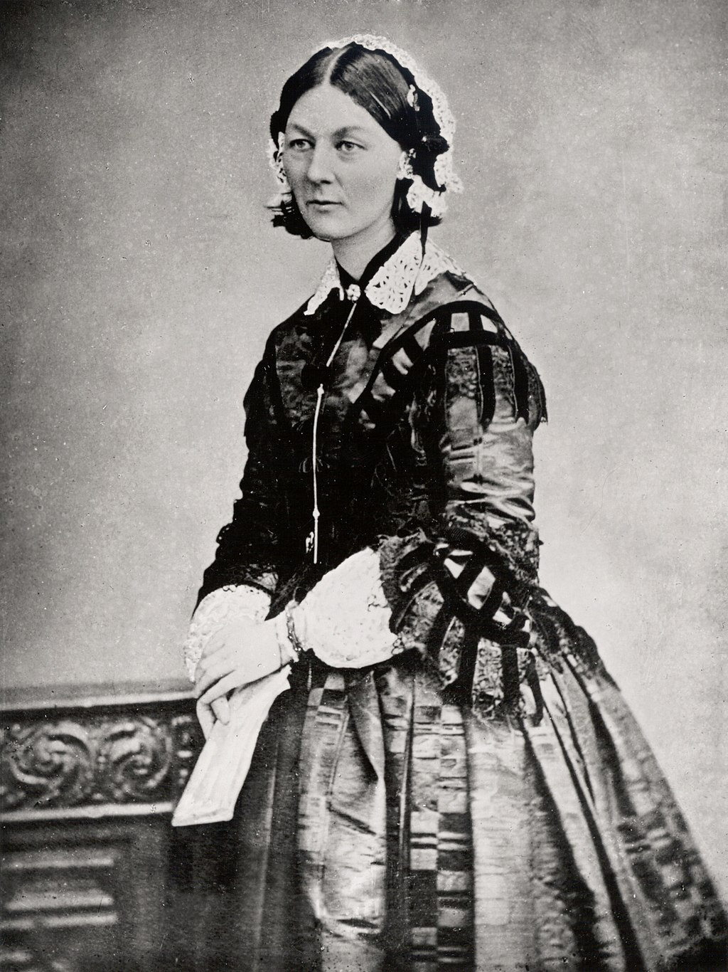 Three quarter portrait of Florence.  she is wearing a lace cap and shirt with a fitted jacket over the top.  She is holding a folded piece of paper in her hands and wears a wide skirt.