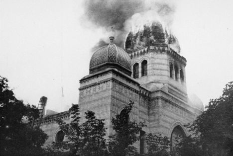 Black and white image of a synagogue on fire.