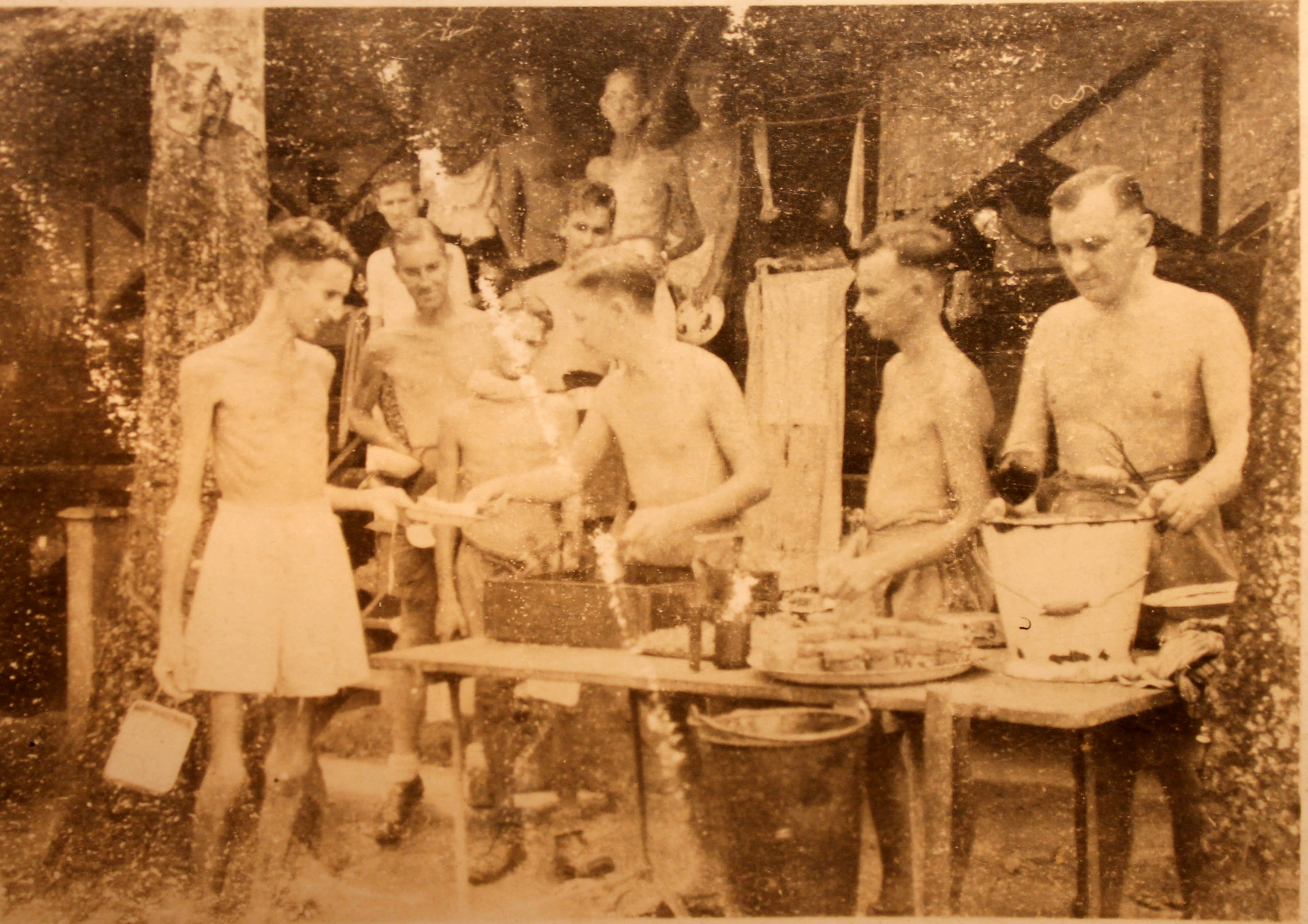 Photograph showing a line of men waiting to be served food. They are all only wearing shorts. Some are very underweight.