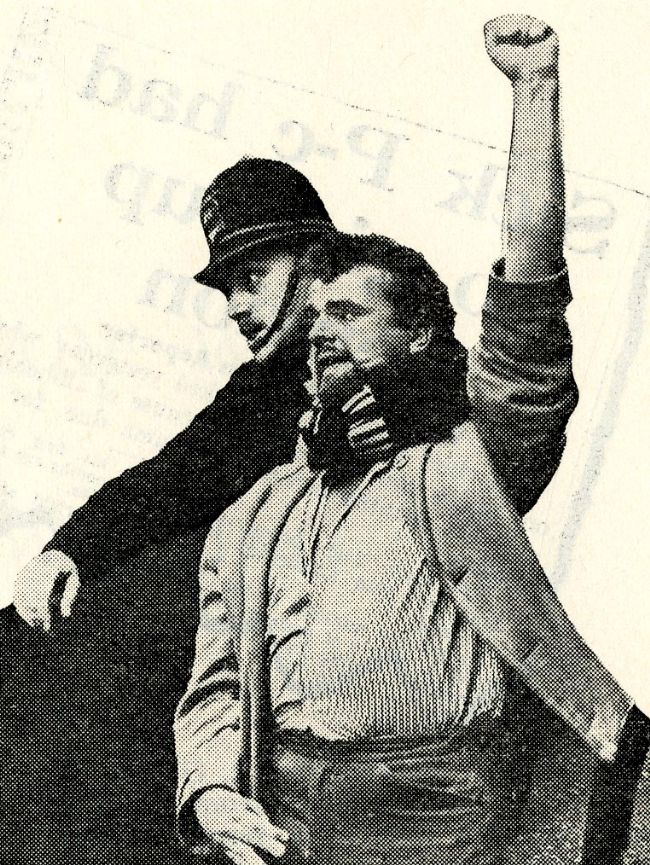 Photograph of policeman with his arm around a protester as he is shouting with his hand in the air
