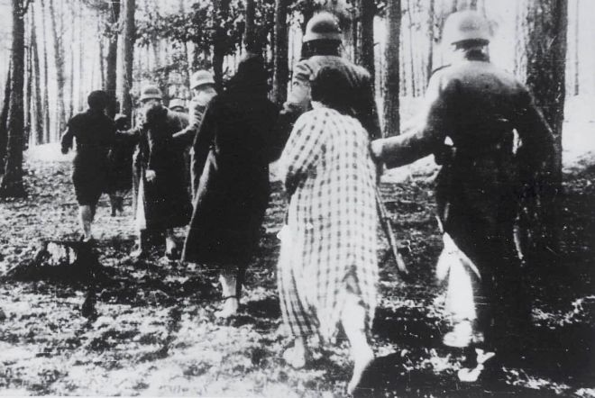 Nazi soldiers leading women and children into a forest to be shot