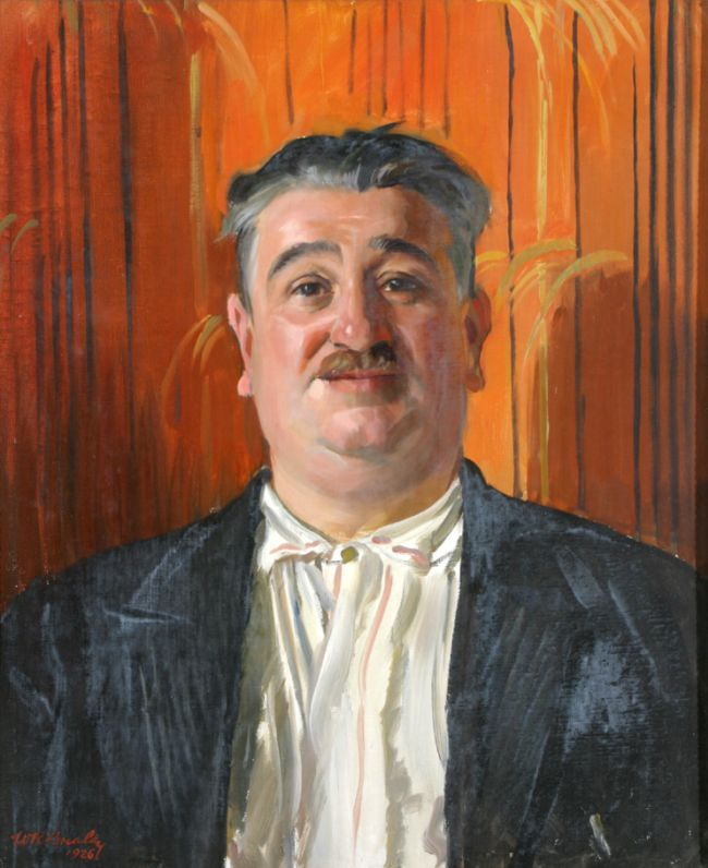 Portrait showing head and shoulders of a man with a moustache and short grey hair. He wears a white shirt with a dark blue jacket and stands against a bright orange background.