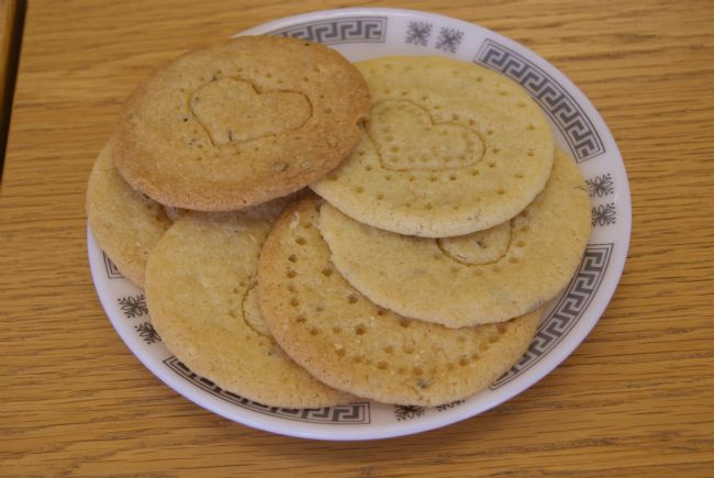 A plate of biscuits stamped with a large heart in the middle and a circle of dots around