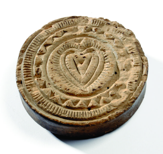 A round wooden  carved stamp with a heart in the middle and circular patterns around it.