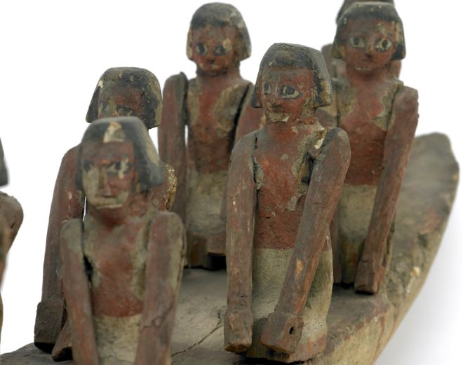 Close up image of the pairs of rowers, their faces are still very distinct.  They have black painted hair and black and white painted eyes.