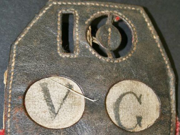 Top half of a lozenge shaped piece of brown leather with the number 10 stamped out of it.  Below are two white circles, one with a 'V' in it and one with a 'G' in it.