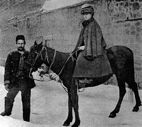 Black and white image of Isabella Bird on a pony near a wall.  There is a Tibetan man holding the reins of the pony