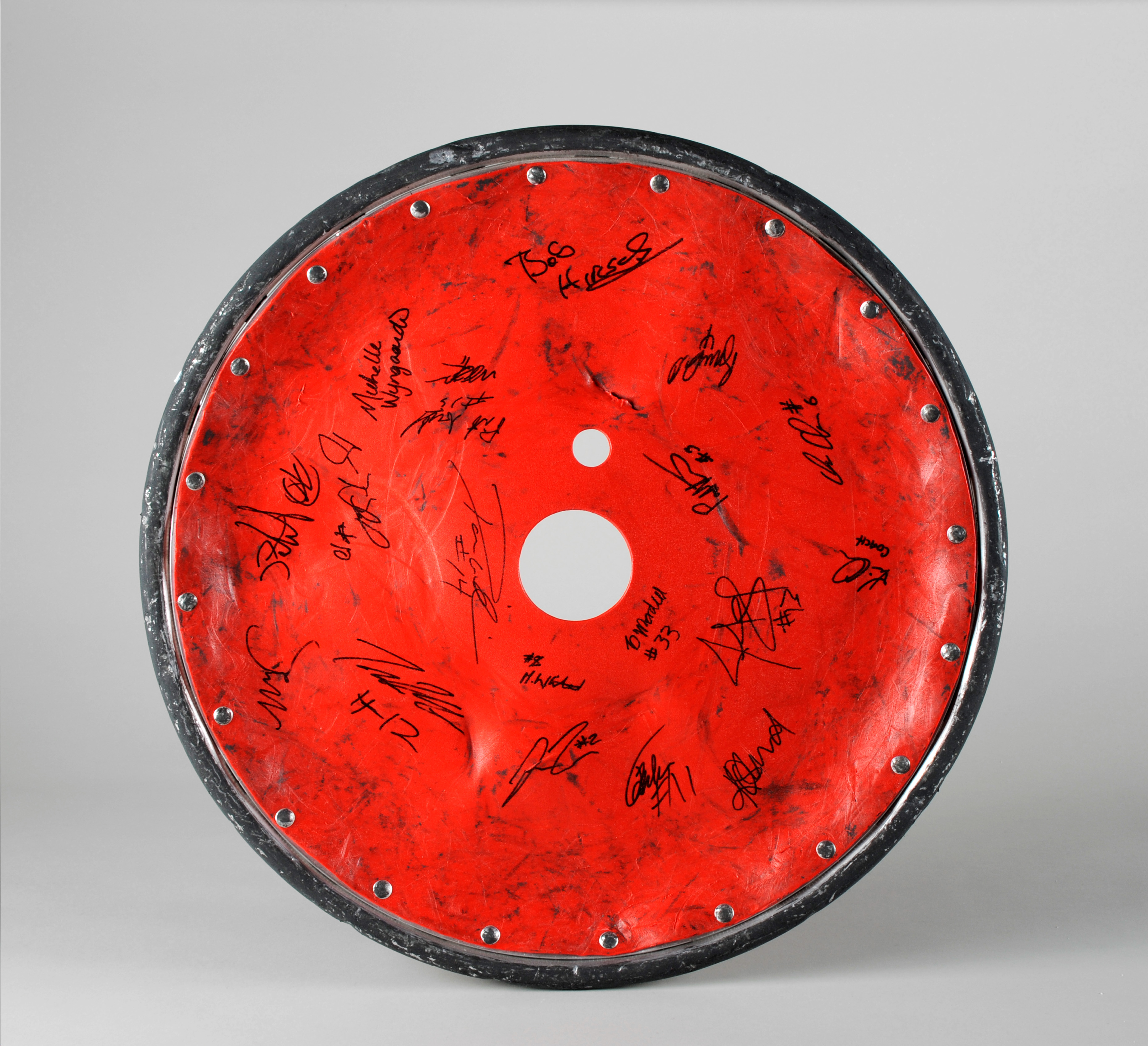 Colour photograph of a wheel, with a red plastic guard. The guard is covered in dents and is ripped.