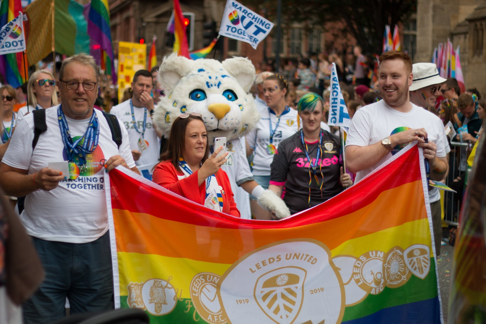 Colour photograph showing a crowd of people marching in the city of Leeds.  At the front several people are holding a large rainbow Leeds United flag