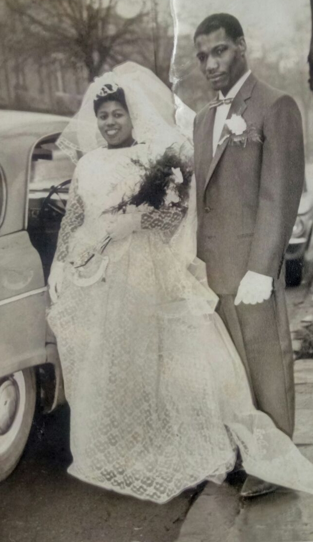 Black and white photograph of a couple of Carribean heritage in their wedding outfits.