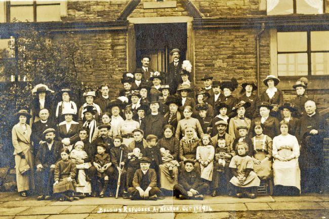Black and white photograph of a group of men, women and children standing outside a house.  There are about 100 people grouped together