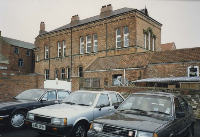 Photo of a two-storey brick building with cars parked in front