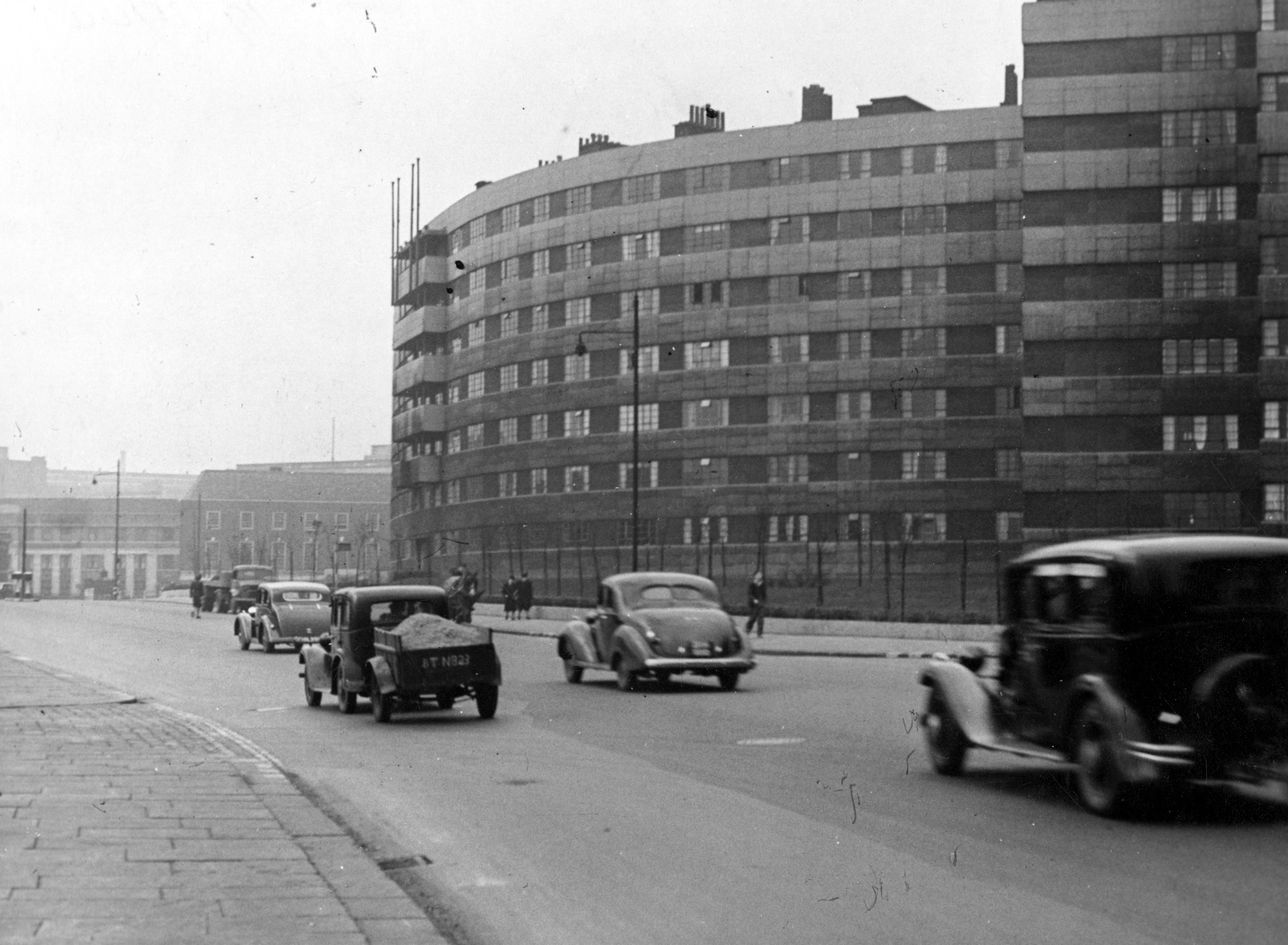 A large building of flats on the left hand side of the photo with a road running past them with cars on.