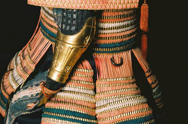 Close up of the waist and hips area of Samurai armour from teh side, showing the strips of armour and metal gauntlets