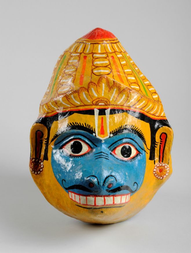 Papier mâché mask of a monkey face, representing the Hindu deity Hanuman. Orissa (now Odisha) state style. Mainly yellow with blue face. Yellow crown or hat has white and red ornament. Teeth barred. Earrings in ears. Forked mark on forehead.