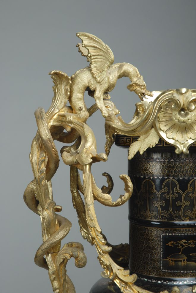 Close up of the gold handles designed as leafy vines and winged beasts.