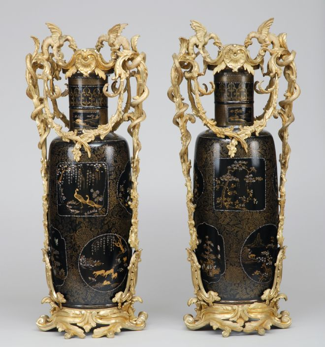 Brown vases with intricate gold handles  of leafy vines and winged beasts.