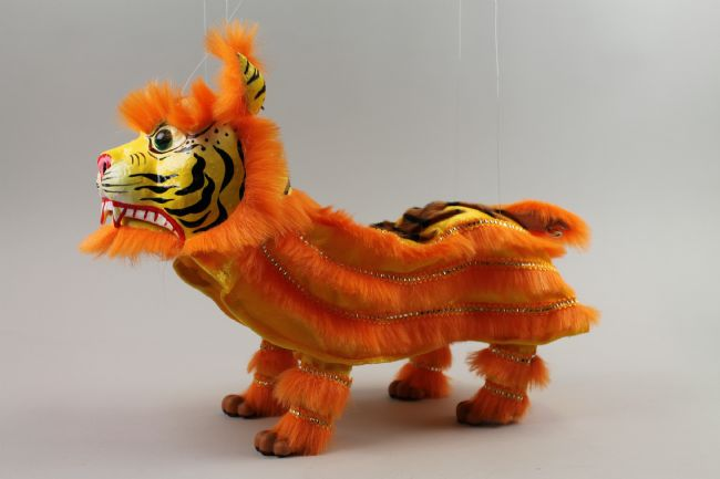 The puppet has a papier mâché head, with a hinged jaw and glass eyes and bells in the ears. Long, orange furry fabric body with small tail and four plastic feet attached.