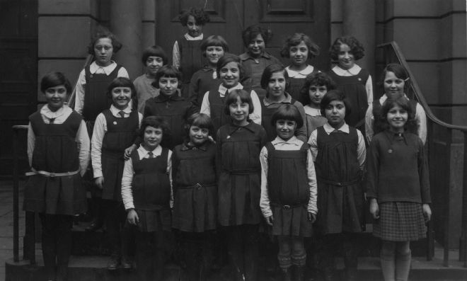 Black and white photograph showing pupils from Hull Hebrew Girls School.  They are wearing dark coloured skirts and jumpers or pinafores with white shirts.