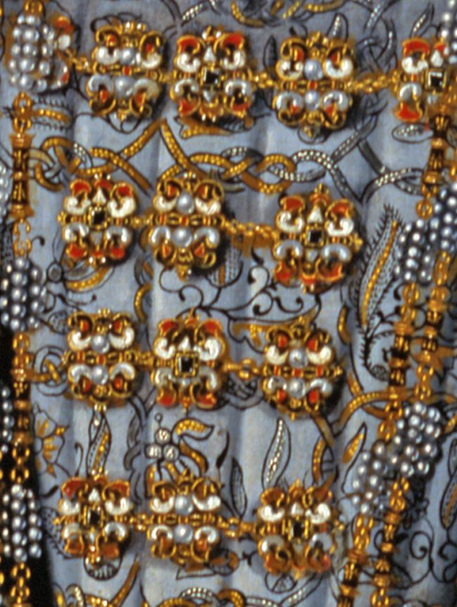 Close up of the dress, showing an elaborate pattern of pearls and gold thread embroidery.