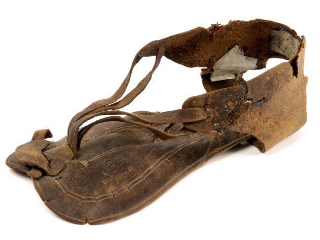 Brown leather sandal with four strips of leather anchoring the foot like a modern flip-flop, attached to leather that goes round the back of the ankle