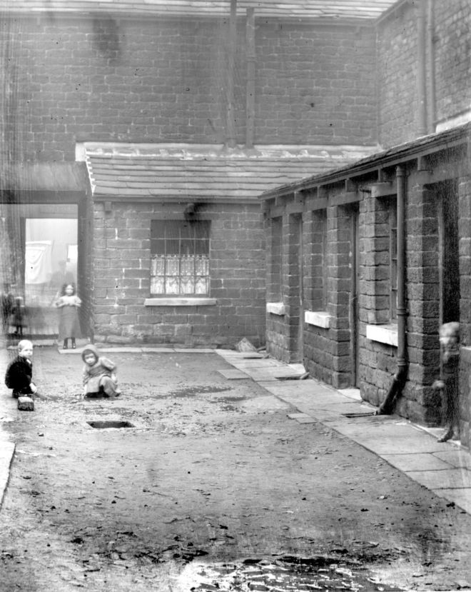 Black and white photograph showing small children playing in Houses in Sykes's Yard, Huddersfield.  There is what looks like an open drain in the street.