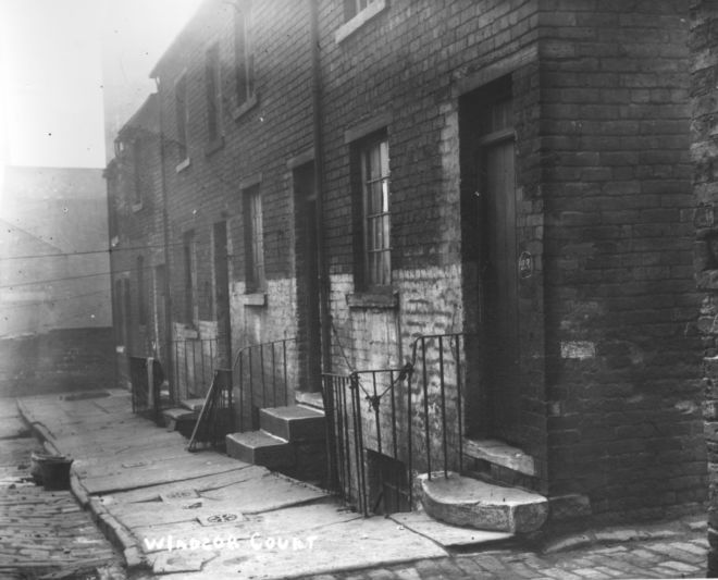 Black and white photo showing Windsor Court, Huddersfield - small terraced houses fronting straight onto the pavement.