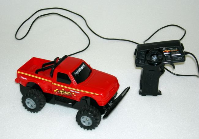 The truck is red with chunky black wheels and is connected to the controller by a wire.