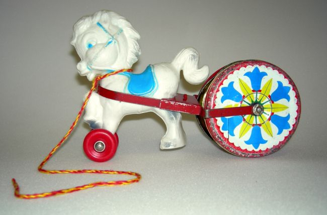 Pull-along toy horse made of plastic and metal musical drum.  The horse is white and has red wheels attached to its front legs.