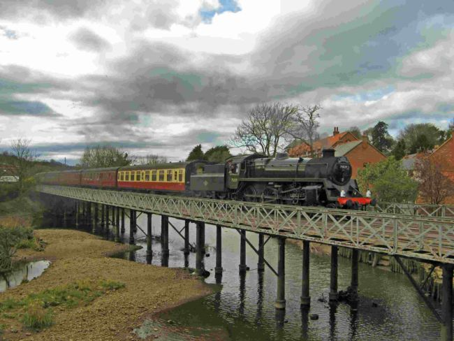 Steam locomotive crossing a river pulling carriages
