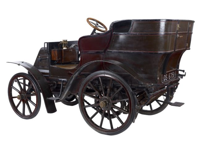 Metal and wood car with a steering wheel.  It looks more robust than earlier models.