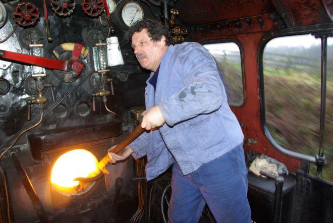 Steam train fireman feeding the fire with a shovelfull of coal
