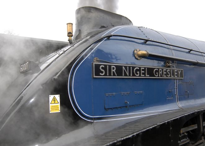 Dark blue and black locomotive with 'Sir Nigel Grelsey' plate on the side.  Steam is coming out of the funnel