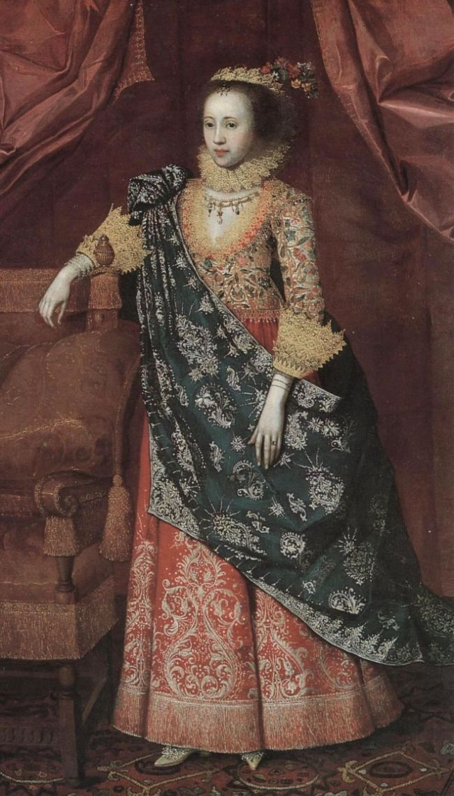 Tudor portrait of Arabella Stuart.  She wears a highly embroidered top and skirt, with more richly decorated material draped over her.  Her face is very pale and her hairline is high.