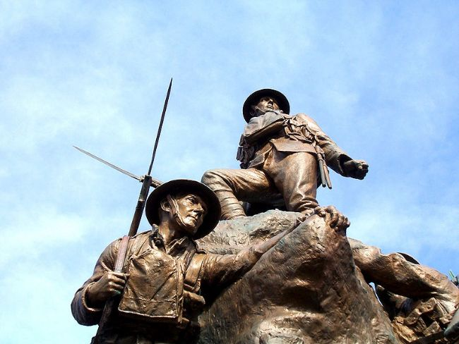 Close up photograph of Oldham war memorial showing two WW1 soldiers wearing helmets and holding bayonets