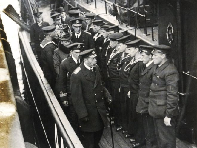 Photograph of King George V and Queen Mary with Lieutenant Commander J H Pitts inspecting a Navy trawler used for minesweeping.  The sailors are lined up in uniform.