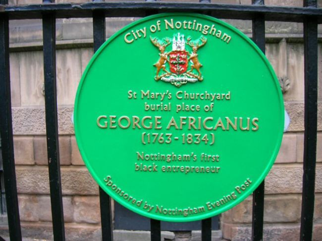 George Africanus Plaque, St Marys Churchyard, Nottingham.  A circular metal plaque, painted green with the city of Nottingham coat of arms on it.