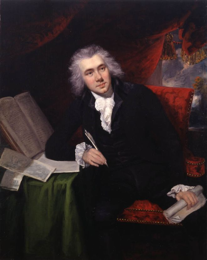 William Wilberforce, oil painting by John Rising, c.1790.  The painting shows William sitting at a desk holding a quill with books opened up  in front of him.