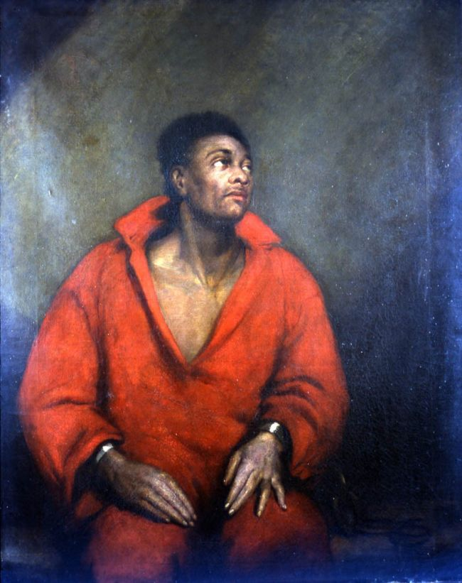 The Captive Slave painting shows a black man wearing an orange jumpsuit.  Metal cuffs can be seen on his wrists