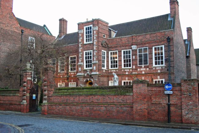 A large brick building with chimneys at either end.