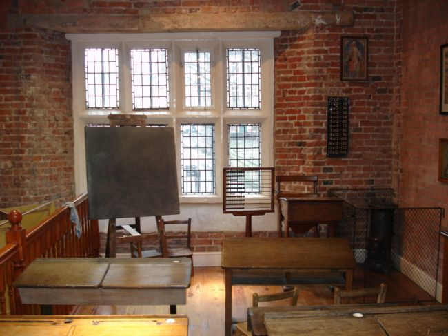 Wooden desks are arranged in rows with a blackboard on an easel at the front and an abacus on a pole.
