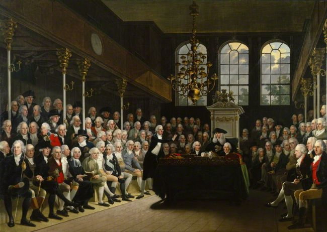 The painting shows a crowded House of Commons .  All the people in the painting are male, many with white hair.