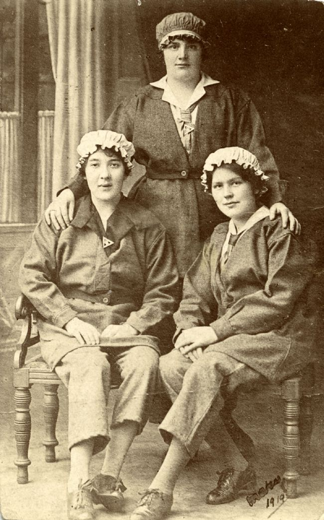 Female Hull munitions workers wearing their uniforms and triangular 'On War Service' badges