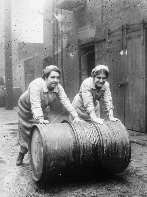 Female workers roll a barrel of varnish in the grounds of Sissons and Co. Ltd, Bankside, Hull in November 1918