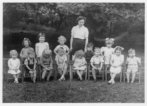 Photograph of a woman with 13 kids sitting outside.