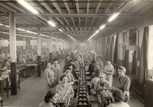 Black and white photograph of women working on a production line in a factory