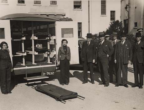 Photograph showing female stretcher bearers standing outside the back of an open ambulance
