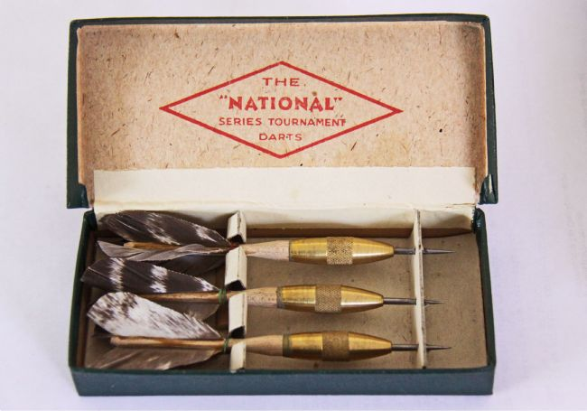 Three darts with real feather flights in a cardboard box.
